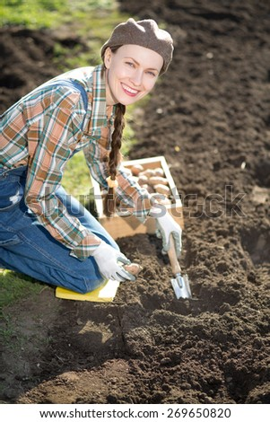 Happy smiling caucasian female farmer or gardener in a hat holding potato going to plant. Agriculture - food production, home grown food concept - stock photo