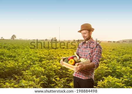 Happy smiling caucasian forty years old farmer in a hat standing proud in front of field landscape holding wooden box with fresh vegetables - agriculture.  - stock photo