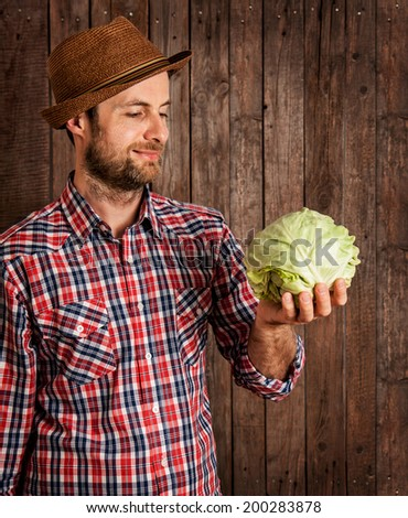 Happy smiling caucasian forty years old farmer or gardener in a hat holding cabbage in hand on rustic vintage planked wood background - agriculture. Food production - vegetables. - stock photo