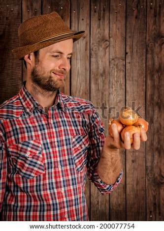 Happy smiling caucasian forty years old farmer or gardener in a hat holding onions in hand on rustic vintage planked wood background - agriculture. Food production - vegetables. - stock photo