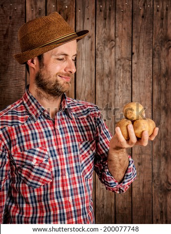 Happy smiling caucasian forty years old farmer or gardener in a hat holding potatoes in hand on rustic vintage planked wood background - agriculture. Food production - vegetables. - stock photo