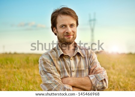 Happy smiling caucasian forty years old farmer standing proud in front of his wheat fields - stock photo