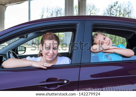 Happy smiling Caucasian mother and child looking at window of car - stock photo