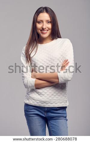 Happy smiling caucasian woman in a carefree stance standing with crossed arms, isolated over gray background - stock photo