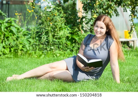 Happy smiling Caucasian woman reading book, sitting on green grass