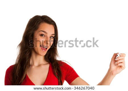 Happy smiling cheerful beautiful young business woman writing or drawing something on screen or transparent glass, by black marker, isolated over white background - stock photo