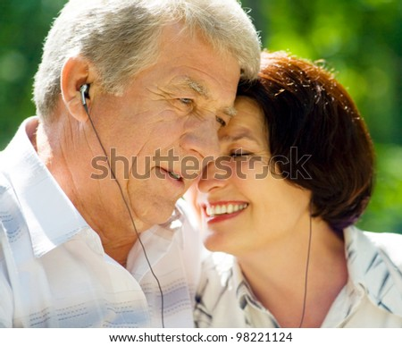 Happy smiling cheerful senior couple listening music or audio book in headset or praying together, outdoors - stock photo