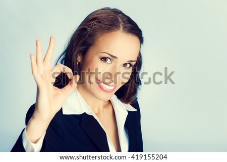 Happy smiling cheerful young business woman with okay gesture - stock photo