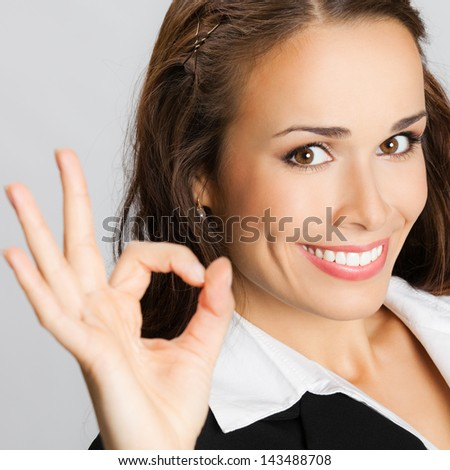 Happy smiling cheerful young business woman with okay gesture, over gray background