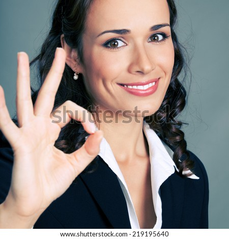 Happy smiling cheerful young business woman with okay gesture, over grey background - stock photo