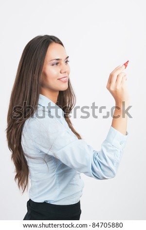 Happy smiling cheerful young business woman writing or drawing on screen with red marker, isolated on white background