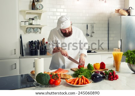 Happy smiling chef with beard preparing a meal with various vegetables, chef in uniform chopping some vegetables for dinner - stock photo