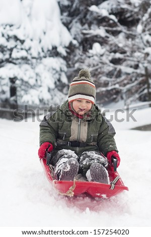 Happy smiling child, boy or girl, sledging in fresh snow in winter.