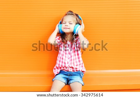 Happy smiling child enjoys listens to music in headphones over colorful orange background - stock photo