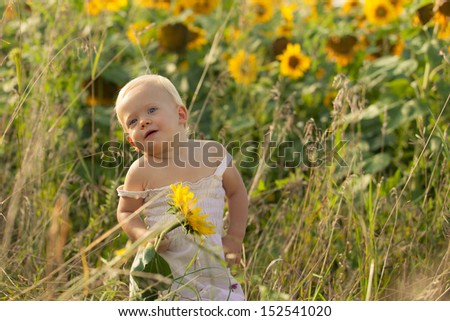 Happy smiling child having fun with sunflowers outdoors in summer on a sunny day.