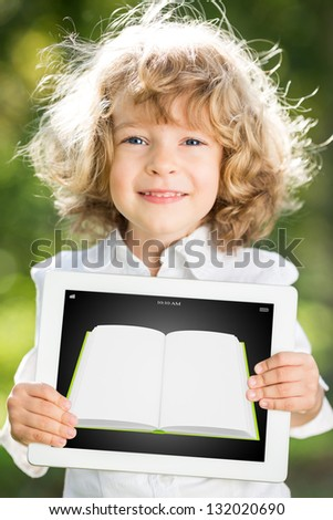 Happy smiling child holding tablet PC with ebook against green spring background. Education technology concept - stock photo