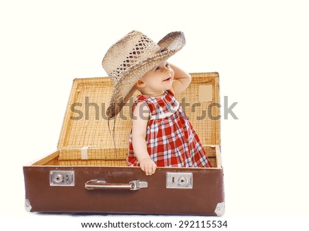 Happy smiling child in straw summer hat sitting on suitcase playing and having fun - stock photo
