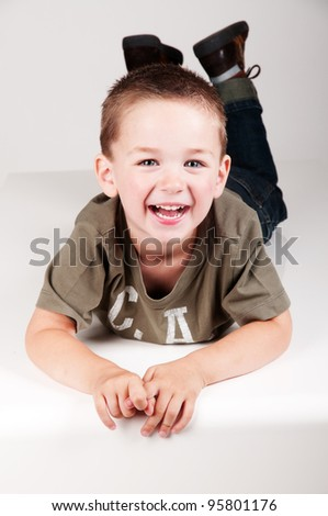 happy smiling child laying on a table - stock photo