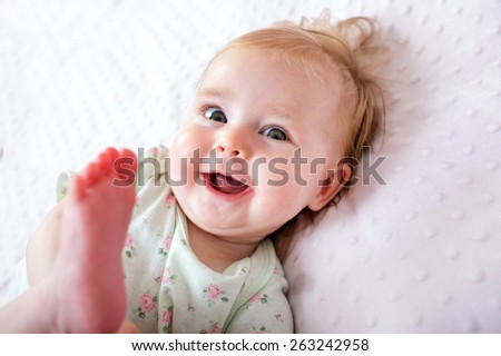 happy smiling child lying in bed - stock photo