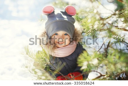 Happy smiling child near christmas tree in winter day - stock photo