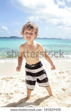 Happy, smiling child on a tropical beach near ocean having fun