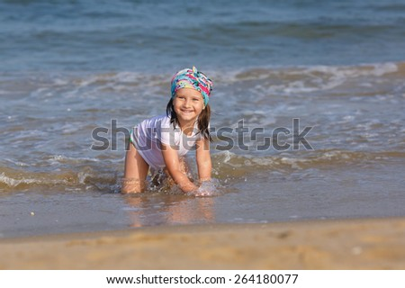 Happy smiling child playing on the beach at the water's edge. Shallow depth of field. Focus on the model.