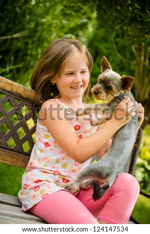 Happy smiling child playing with their pet - outdoor in backyard - stock photo