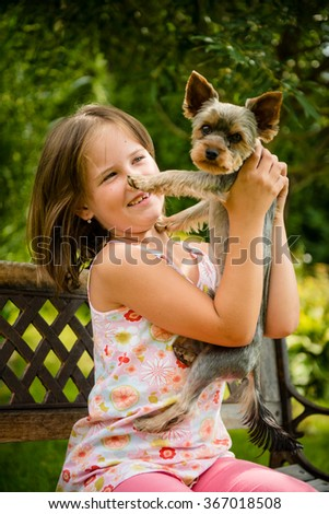 Happy smiling child playing with their pet - outdoor in backyard