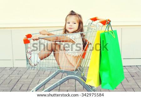 Happy smiling child sitting in trolley cart with colorful shopping bags having fun - stock photo