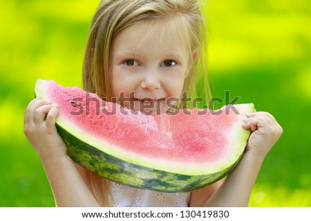 Happy smiling child sitting on green grass in park and eating watermelon - stock photo