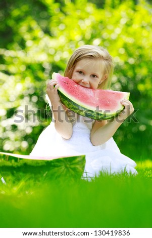 Happy smiling child sitting on green grass in park and eating watermelon