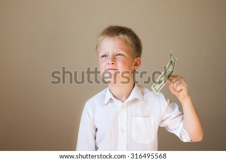 Happy smiling child with money (20 dollars) in hand on grey background