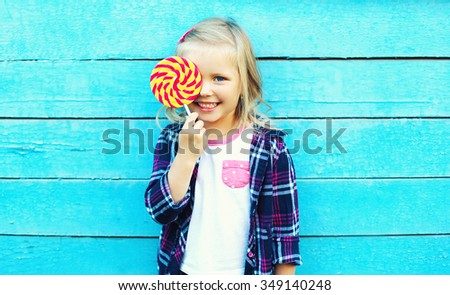 Happy smiling child with sweet lollipop having fun over colorful blue background - stock photo