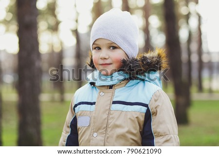 Happy, smiling children, kids, baby boy plays in nature in the park, in the woods.