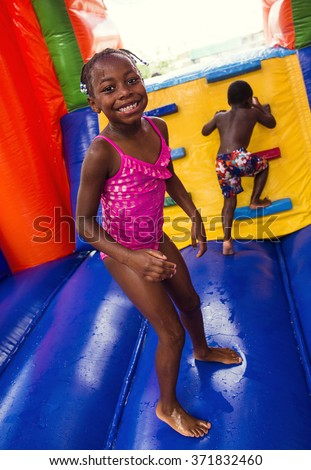 Happy smiling children playing on an inflatable bounce house - stock photo