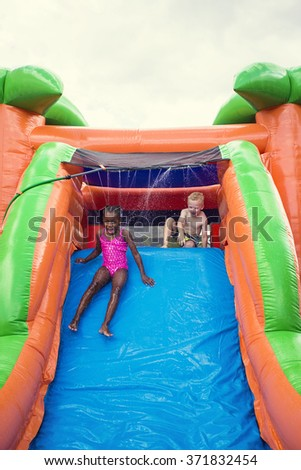 Happy smiling children playing on an inflatable slide bounce house - stock photo