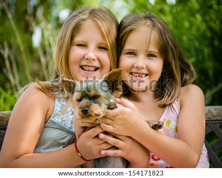 Happy smiling children playing with their pet - outdoor in backyard