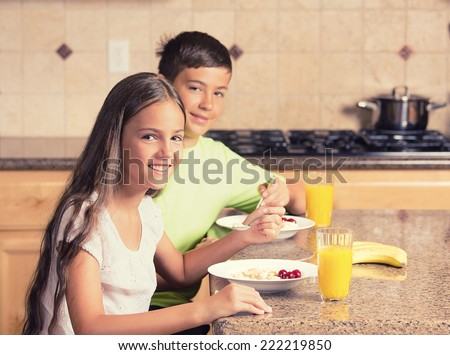 happy smiling children teenager girl and boy, siblings eating cereal with milk and drinking orange juice for breakfast in the kitchen. Positive face expressions, emotions - stock photo