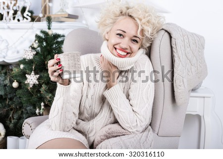 Happy smiling Christmas woman in Knitted stylish clothes. Cozy decorated light holiday interior. Series of winter holiday photos. - stock photo