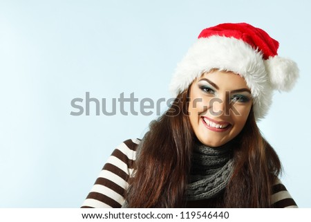 happy smiling christmas woman in santa's red hat, winter girl over blue background - stock photo