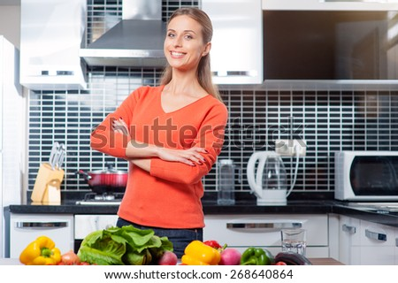 Happy smiling confident woman with crossed arms in kitchen with fresh produce vegetables preparing for a healthy meal - stock photo