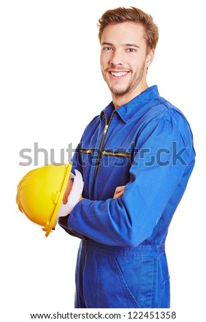 Happy smiling construction worker with yellow hardhat in blue overall - stock photo