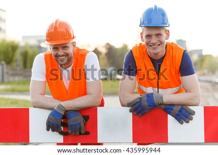 Happy smiling construction workers looking into the camera - stock photo