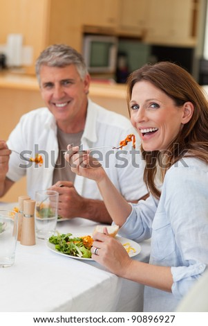 Happy smiling couple eating dinner together - stock photo