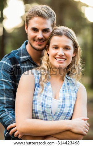 Happy smiling couple embracing and looking at the camera in the nature - stock photo
