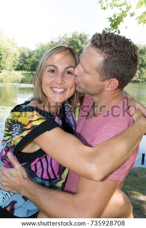 Happy smiling couple embracing and looking at the camera in the nature