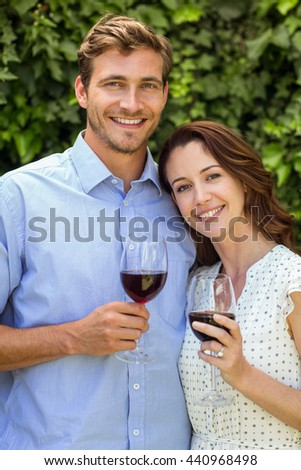 Happy smiling couple holding wineglasses at front yard - stock photo
