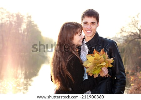 Happy smiling couple in love having fun autumn bright sunny day backlit - stock photo