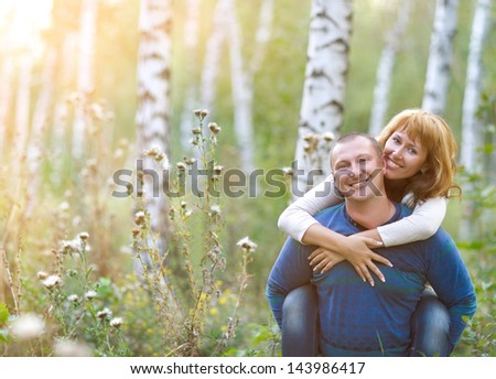 Happy smiling couple in the autumn forest. Sunset