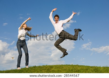 Happy smiling couple  jumping in blue sky - stock photo